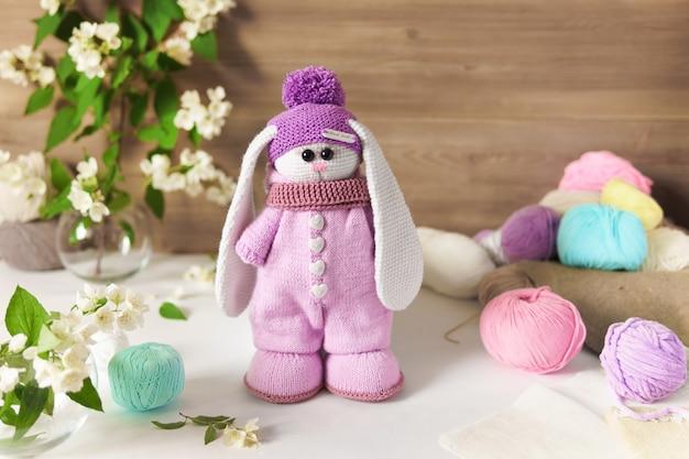 Um coelho feito de fios de lã. brinquedo de pelúcia de malha artesanal sobre uma mesa de madeira.