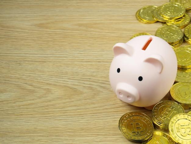 Um cofrinho com bitcoins na mesa de madeira