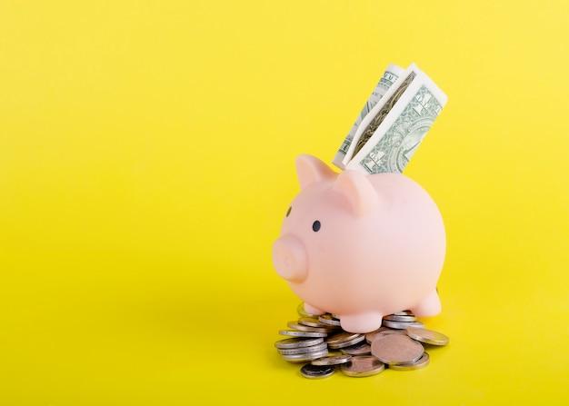 Um cofrinho rosa com dólares americanos e moedas em fundo amarelo
