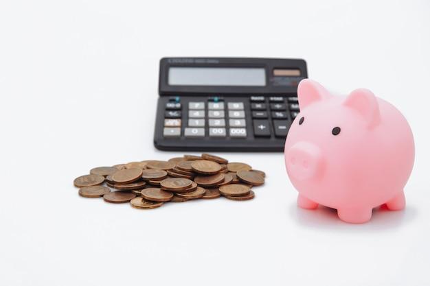 Um cofrinho rosa, dinheiro e calculadora em branco.