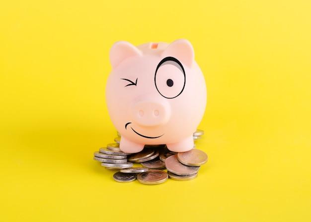 Um cofrinho sorridente na pilha de moedas no fundo amarelo