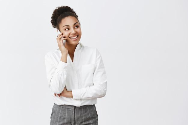 Um colega de trabalho faminto chamando a entrega de comida para vir rapidamente. charmosa, feliz e confiante chefe feminina criativa de camisa e calça, falando via smartphone, olhando de lado, tendo uma conversa interessante