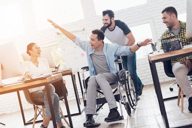 Um colega rola uma pessoa em uma cadeira de rodas ao redor do escritório