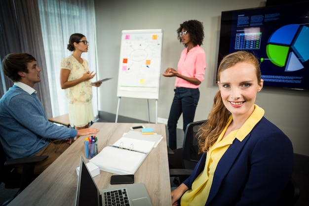 Um colega sorrindo para a câmera enquanto colegas de trabalho discutem fluxograma no quadro branco