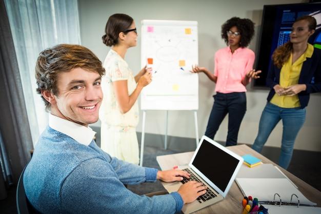 Um colega usando laptop sorrindo para a câmera enquanto colegas de trabalho discutem fluxograma no quadro branco