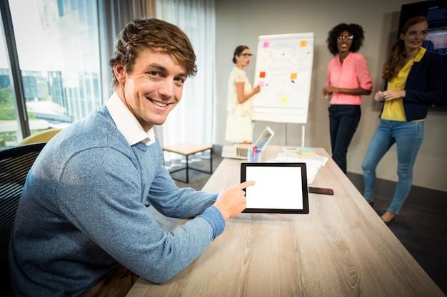 Um colega usando tablet digital enquanto colegas de trabalho discutem fluxograma no quadro branco