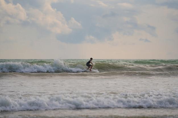 Um com um surf em suas mãos na costa do mar