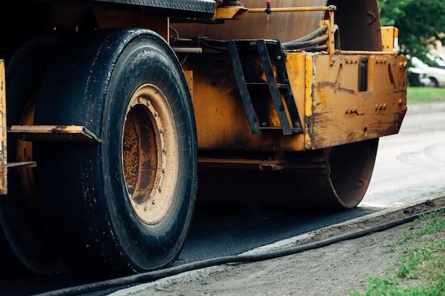 Um compactador de asfalto amarelo alinha a estrada. colocação de novo asfalto.