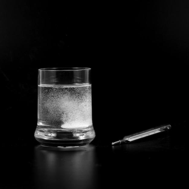 Um comprimido efervescente no copo com um termômetro ao lado para medir a febre