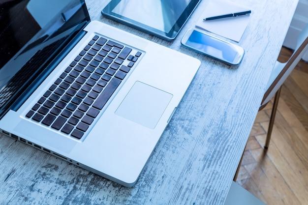 Um computador laptop, um tablet pc e um smartphone em uma área de trabalho.