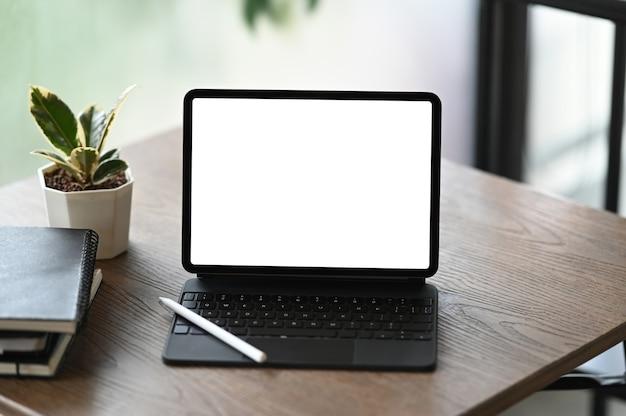 Um computador tablet, notebooks e planta de casa na mesa de madeira.
