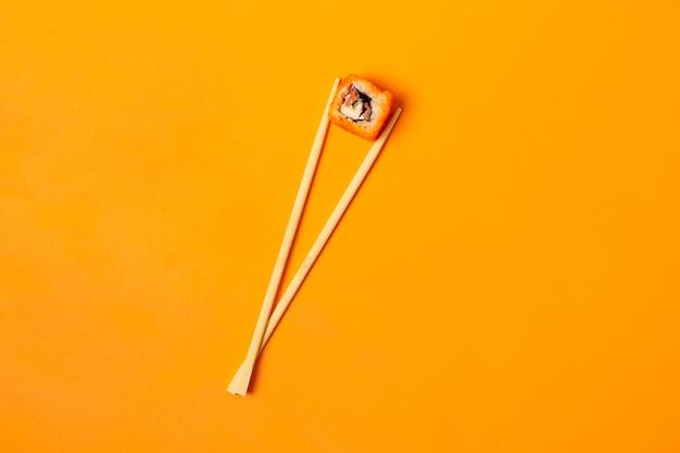 Um conceito abstrato dos pauzinhos de madeira asiáticos com um rolo de comida nacional na superfície colorida