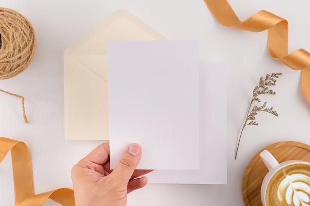 Um conceito de casamento. cartão do convite do casamento no fundo branco com fita e decoração.