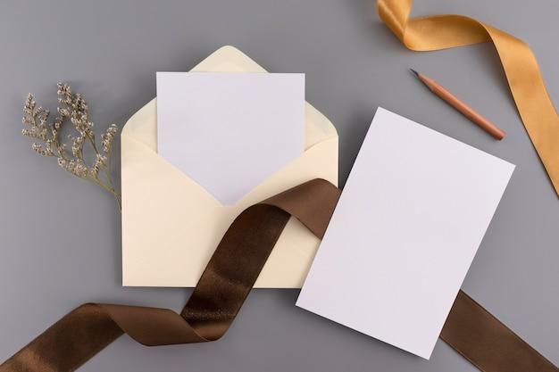 Um conceito de casamento. cartão do convite do casamento no fundo cinzento com fita e decoração.