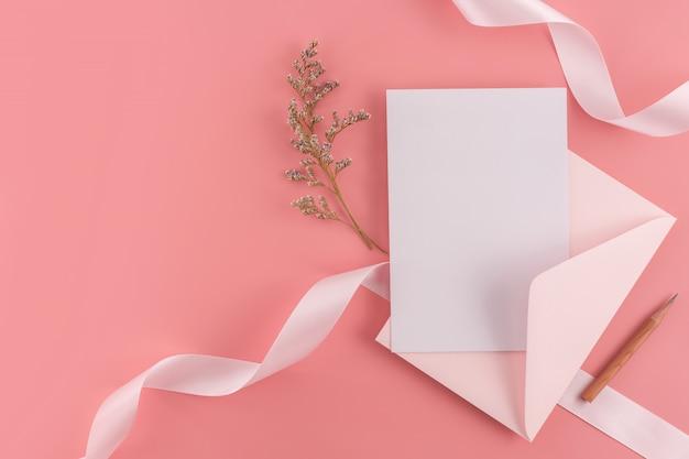 Um conceito de casamento. cartão do convite do casamento no fundo cor-de-rosa com fita e decoração.