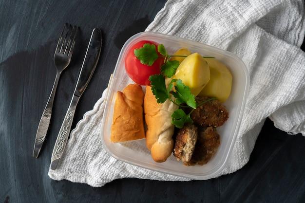 Um conceito de hora de almoço, comendo do recipiente de plástico com carne e batatas nas mesas