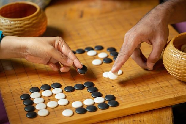 Um concorrente está colocando uma peça de mármore em um jogo de tabuleiro go.