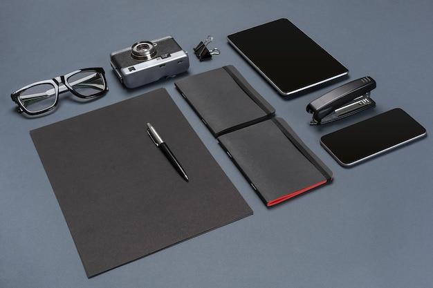 Um conjunto de acessórios de escritório pretos, óculos, câmera velha e tablet em fundo cinza. postura plana. ainda vida. brincar
