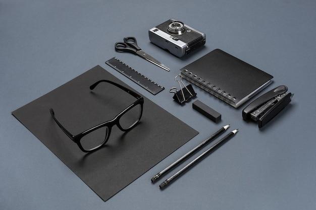 Um conjunto de acessórios de escritório pretos, óculos e câmera velha em fundo cinza. postura plana. ainda vida. brincar