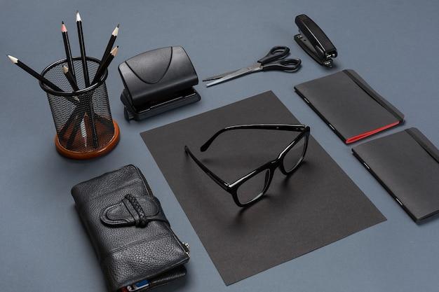 Um conjunto de acessórios de escritório pretos, óculos em fundo cinza. postura plana. ainda vida. brincar