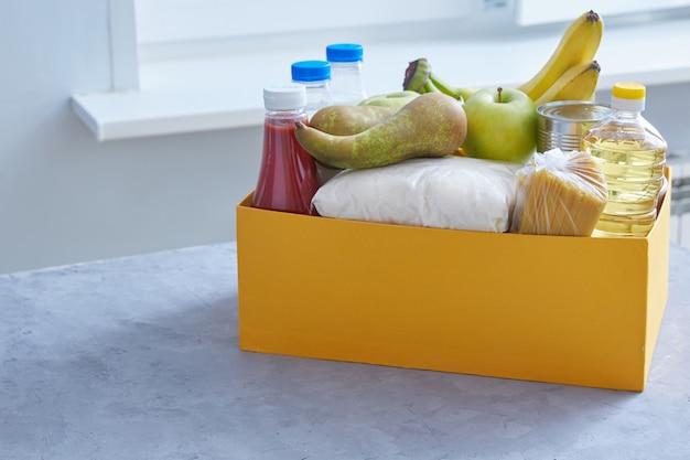 Um conjunto de alimentos para alimentos em uma caixa amarela. copie o espaço em um fundo cinza-azul. doação ajuda pobres, desempregados