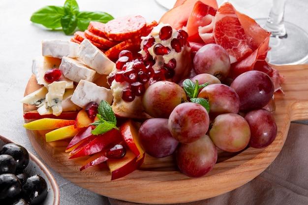 Um conjunto de aperitivos para vinho, jamon, calabresa, queijo, uvas, pêssego e azeitonas em uma placa de madeira close-up. snack board na mesa.