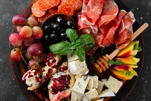 Um conjunto de aperitivos para vinho, jamon, pepperoni, queijo, uvas, pêssego e azeitonas em uma vista superior da placa de madeira.