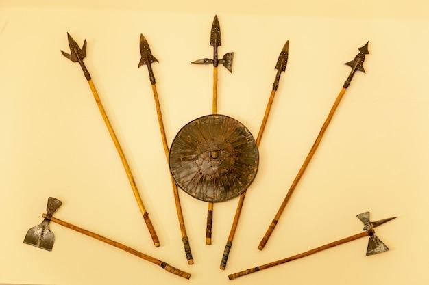 Um conjunto de armas medievais. lanças, machados, escudo em fundo bege.