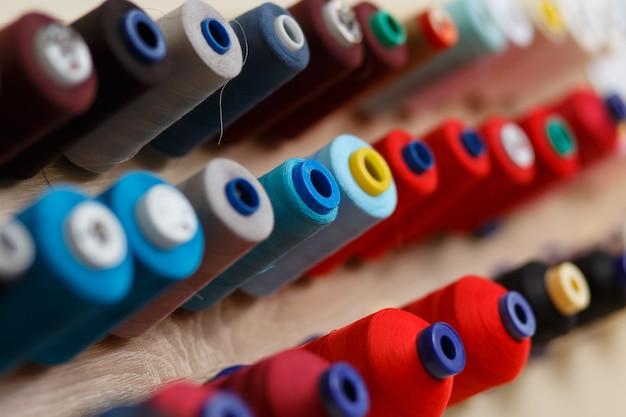 Um conjunto de bobinas com linhas coloridas na oficina de costura.