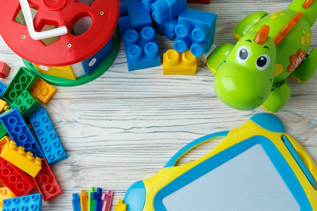 Um conjunto de brinquedos infantis em desenvolvimento coloridos sobre um fundo de madeira. jogos educativos para crianças com espaço para texto