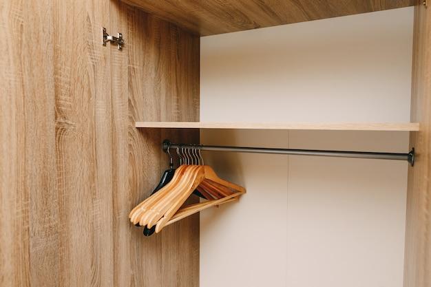 Um conjunto de cabides no armário em uma barra de cabide sob a prateleira com portas abertas