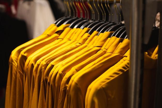Um conjunto de camisas amarelas penduradas em um cabide em uma boutique de moda.