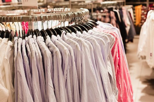 Um conjunto de camisas clássicas azuis penduradas em um cabide em uma boutique de moda.