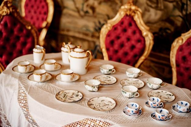 Um conjunto de chá com um padrão azul e um conjunto dourado em uma bandeja sobre uma lareira branca