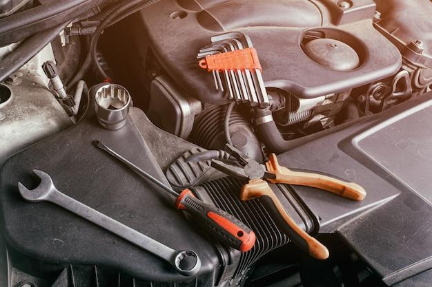 Um conjunto de chaves inglesas, chaves de fenda, alicates e catraca de tamanhos diferentes fica embaixo do capô do carro em um radiador de óleo. conceito de reparação de automóveis e ferramentas no serviço de carro