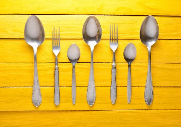 Um conjunto de colheres e garfos em uma mesa de madeira amarela. vista do topo.