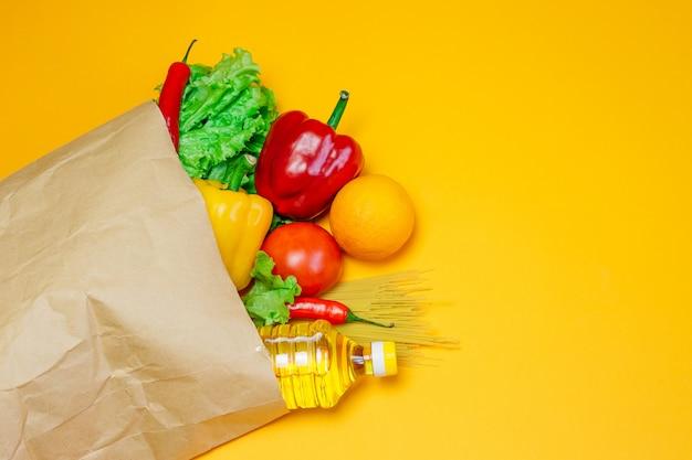 Um conjunto de comida vegan, pimenta, pimentão, óleo de girassol, tomate, laranja, macarrão, alface no pacote de papel ofício isolado em um espaço laranja