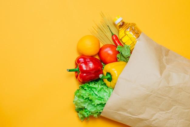 Um conjunto de comida vegetariana, pimenta, pimentão, óleo de girassol, tomate, laranja, macarrão, alface no pacote de papel artesanal, em um espaço laranja