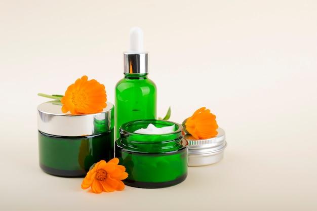 Um conjunto de cosméticos para cuidados com o rosto e corpo. garrafas verdes e flores de calêndula