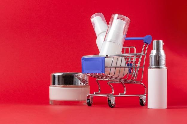 Um conjunto de cosméticos para rosto e corpo e um carrinho de compras em um fundo vermelho brilhante. o conceito de compra de cosméticos, loja online, férias