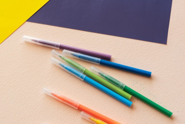 Um conjunto de criatividade e desenvolvimento infantil. canetas hidrográficas, papel colorido sobre a mesa.