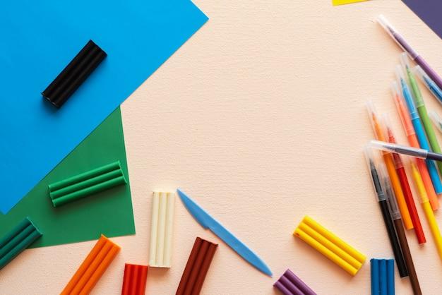 Um conjunto de criatividade e desenvolvimento infantil. plasticina, canetas hidrográficas, papel colorido em cima da mesa. lugar para o seu texto