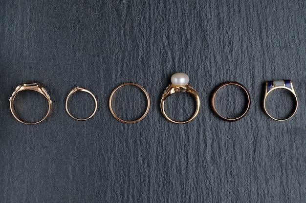 Um conjunto de diferentes anéis de ouro em uma placa de pedra preta. vista do topo.