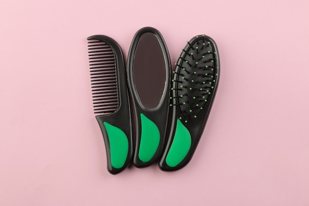 Um conjunto de diferentes escovas de cabelo e um espelho em um só estilo em um fundo rosa brilhante. vista de cima
