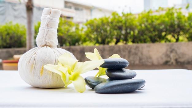 Um conjunto de diferentes itens de massagem e pedra preta, precisa de spa ou massagem tailandesa no banco branco.