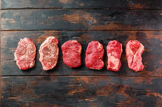 Um conjunto de diferentes tipos de bifes de carne crua: lâmina superior, alcatra, rolo de olho de mandril sobre o antigo espaço de vista superior do fundo de madeira para texto.