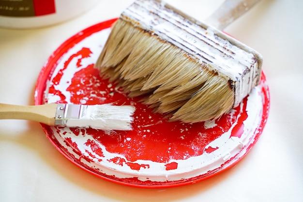 Um conjunto de equipamentos para pintura de conserto de apartamentos e lata de tinta de design no chão