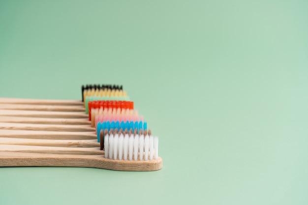 Um conjunto de escovas de dentes antibacterianas ecológicas feitas de madeira de bambu em um fundo verde claro. tendências de cuidado ambiental.