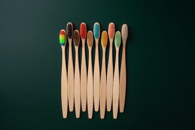 Um conjunto de escovas de dentes antibacterianas ecológicas feitas de madeira de bambu em um fundo verde escuro. tendências ambientais.