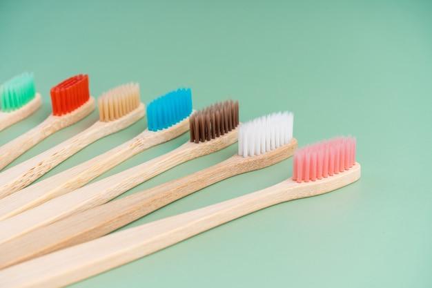 Um conjunto de escovas de dentes antibacterianas ecológicas feitas de madeira de bambu em uma superfície verde clara. tendências de cuidado ambiental.